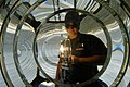 US Navy 040813-N-5328N-004 Electrician's Mate 3rd Class Ryan Pritchard looks through the center of a fresnel lens while testing a new lamp to ensure it is working properly, at the lighthouse on board Naval Air Station (NA.jpg