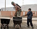 US Navy 070810-N-0194K-156 EO1 Manuel Gradillas, assigned to Construction Battalion Maintenance Unit (CBMU) 202, and a local boy, shovel rocks to mix into concrete at Miguel Grau School.jpg