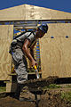 US Navy 080818-N-1508S-155 Airman 1st Class Jonathan Oliver, embarked aboard the amphibious assault ship USS Kearsarge (LHD 3), lays the foundation to a walkway leading to training centers under construction at the Regional Gov.jpg