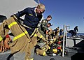 US Navy 090723-N-2638R-003 U.S. and Australian midshipmen aboard Arleigh Burke-class guided-missile destroyer USS Mustin (DDG 89) race to properly don their fire fighting gear.jpg