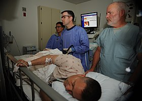 US Navy 110405-N-KA543-028 Hospitalman Urian D. Thompson, maldekstro, Lt. Cmdr. Eric A. Lavery kaj Registered Nurse Steven Cherry revizias la ekranwhil.jpg