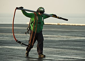 US Navy 120105-N-BT887-025 Logistics Specialist Seaman Tyler Thibault carries a hook across the flight deck during vertical replenishment aboard th.jpg