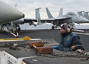 US Navy 120209-N-JV638-030 Aviation Boatswain's Mate (Handling) Airman Mitch Bogrett moves a jet into a spot on the flight deck of the aircraft car.jpg