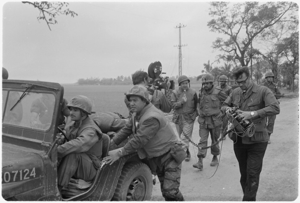 Vietnam. Walter Cronkite and a CBS Camera crew use a jeep for a dolly during an interview with the commanding officer... - NARA - 532454