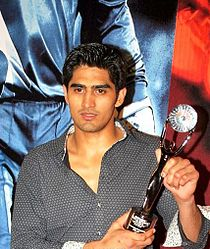 Picture of a young Indian male up to the waist. He has sharp features and short cropped black hair. He wears a black shirt and holds a trophy in his left hand