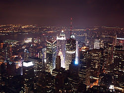 A aerial view of skyscrapers at night. Most of the buildings are lit up with lights coming from the inside of them. In the background, a dark sky with no clouds can be seen.