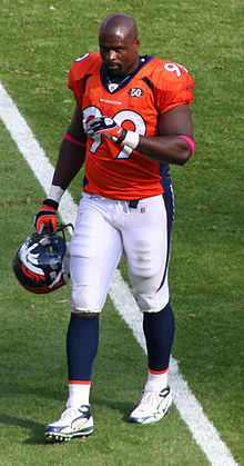 An American football player wearing an orange jersey with blue and white bottoms while walking.