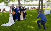 A man in a blue shirt and dark pants at right crouches as he takes a picture of a group of people at left in formal wear, with a woman in a white wedding dress at the rightmost. Behind them are tall trees and a large lake