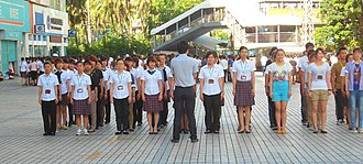 Pre-work assembly - Mall workers standing in formation before their morning shift in Haikou, Hainan, China.
