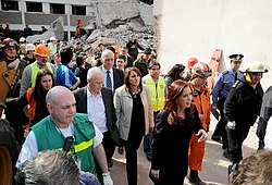 Woman walking through a disaster area with many other people