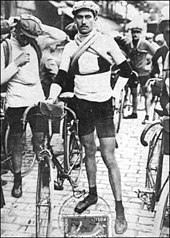 A man standing next to his bicycle; more men and bicycles in the background.