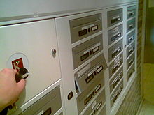 A number of letterboxes beside an electronic keyreader. A hand is holding an electronic key up to the reader, and one of the boxes is automatically opening.