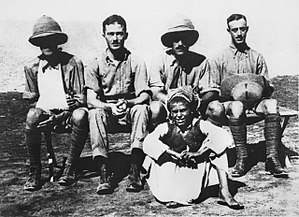 Four men in khaki military uniforms, two wearing pith helmets (one of whom has his arm in a sling), seated behind a boy