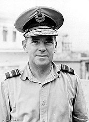 Outdoor head-and-shoulders portrait of man in light-coloured shirt with shoulder insignia, wearing peaked cap with two rows of braid