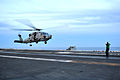 A U.S. Sailor directs an MH-60 Seahawk helicopter assigned to Helicopter Maritime Strike Squadron (HSM) 78 to land on the flight deck of the aircraft carrier USS Ronald Reagan (CVN 76) in the Pacific Ocean 131109-N-EC099-238.jpg