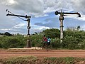 A lady rides a bicycle with a passenger along the train tracks in Lira town, Uganda.jpg