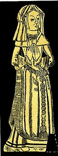 A woman in a long gown standing with hands clasped prayer-like in front of  her. She wears a gable  headdress and veil, a fur-lined gown over a kirtle with a girdle or belt. There are large paternoster beads attached to her decorative belt by a three-rose buckle.