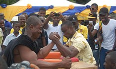Two alumni engage in an arm wrestling contest