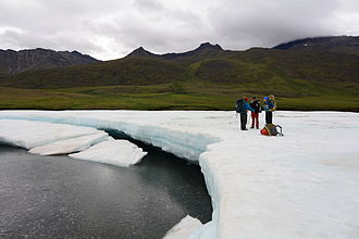 Aufeis - Backpackers cross a sheet of aufeis in the Anaktuvuk River Valley of Alaska