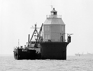 Baltimore Harbor Light - Baltimore Light being fitted with a radioisotope thermoelectric generator on May 20, 1964, making it the first and only nuclear-powered lighthouse in the United States. In the background is the NS ''Savannah'', the first nuclear-powered merchant vessel.