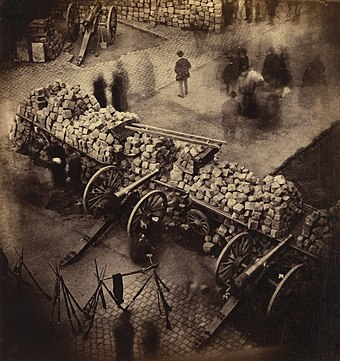 A barricade constructed by the Commune in April 1871 on the Rue de Rivoli near the Hotel de Ville. The figures are blurred due to the camera's lengthy exposure time, an effect commonly seen in early photographs. Barricade Paris 1871 by Pierre-Ambrose Richebourg.jpg