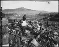 Battered religious figures stand watch on a hill above a tattered valley. Nagasaki, Japan. - NARA - 532564.tif
