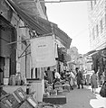 Bedrijvigheid op de markt, op de voorgrond een affiche op een vlag, Bestanddeelnr 255-2488.jpg