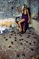 Blond woman on a Purple dress near several plastic spiders.jpg