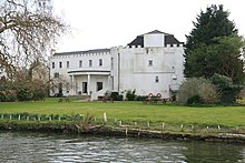 Colour photograph of a large white building with a castellated roof surrounded by trees situated in front of a river