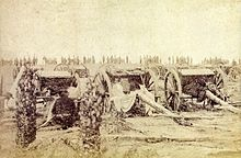 An old photograph showing a group of field artillery pieces and caissons with a line of soldiers in the background