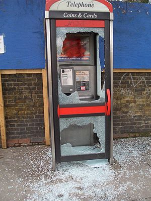 A telephone booth with smashed tempered glass ...