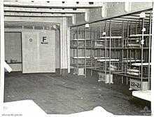 "Inside of a medical ward aboard a ship: Bunk beds line the right side, other furnishings protrude into the bottom edge of the photograph, but apart from these, the room is empty. A door at the far end of the room has the text ""F WARD"" painted on it."