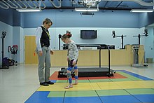 A girl wearing leg braces walks towards a woman.  They are standing in a gym, and a treadmill is visible in the background.