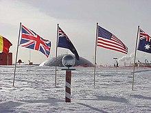 Il polo sud cerimoniale, circondato dalle bandiere degli stati aderenti al Trattato Antartico