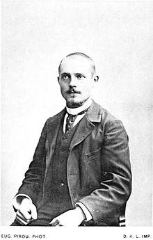 Fotografia monocromática de um homem sentado, de frente.