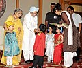 Children tying 'Rakhi' to the Prime Minister, Dr. Manmohan Singh, on the occasion of 'Raksha Bandhan', in New Delhi on August 13, 2011. Smt. Gursharan Kaur is also seen (2).jpg