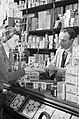 Customer making a purchase in a grocery shop during the Second World War. D2374.jpg