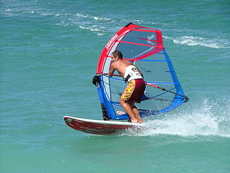 Windsurfing - A windsurfer tilts the rig and carves the board to perform a planing (or carve) jibe (downwind turn) close to shore at Maui, Hawaii