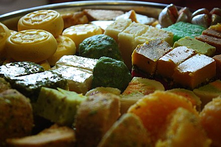 A tray of South Asian sweets, with some pieces covered with shiny silver vark Diwali sweets India 2009.jpg