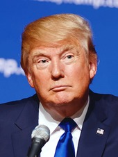 Headshot of presidential candidate Donald Trump, wearing a suit and behind a microphone