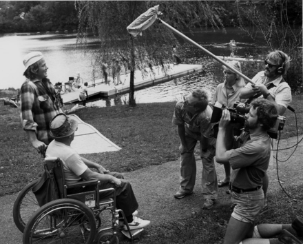 On location outside Baltimore, cameraman Jim Furrer, sound recordist Bill Porter, and director David Ryan interview participants in a public rowing clinic as part of an early electronic journalism shoot in the 1980s. Electronic journalism crew shooting interview on location.png