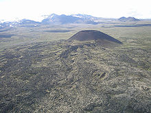 An open cone-shaped mountain rising above a plateau with a glaciated mountain towering in the background.