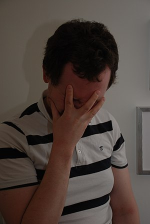 English: A man making the facepalm gesture.