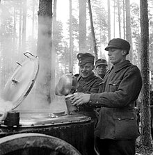 During additional refresher training, a Finnish soldier is having his breakfast served into a mess kit by another soldier from a steaming field kitchen in the forests of the Karelian Isthmus. More soldiers, two of them clearly visible, are waiting in line for their turn behind him. It is early October and the snow has not set in yet.
