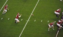 A holder receives the snap with the kicker preparing to kick the ball.
