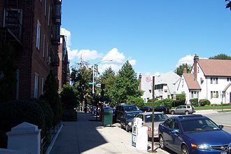 Forest Hills, Queens - Southeastern portion of Austin Street with typical Queens six-story red brick apartment buildings on one side and residential homes on the other