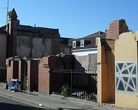 A vacant space is surrounded by a weathered wall and gate. Behind the space stands two buildings, the one on the left looking somewhat decrepit while the one in the middle looking better taken care of.