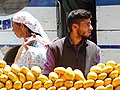 Fruit Vendor with Passerby - Old City - Srinagar - Jammu & Kashmir - India (26219281324).jpg