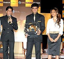 Two middle-aged males and one female standing. The man in the middle wears a black suit and carries a golden colored casket. The other man to his right wears a black suit and speaks in a microphone. The lady on the left wears a white shirt and black skirt. Her hair is brownish and falls in locks around her.