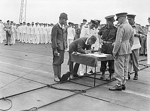General Imamura signing the official document of surrender for Japanese forces in New Britain, New Ireland, the Solomons and New Guinea, on the flight deck of HMS GLORY off Rabaul, 12 September 1945. A30498.jpg
